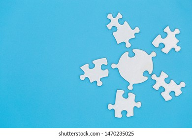 Unfinished white jigsaw puzzle on blue background with copy space. Business strategy teamwork and problem solving concept.