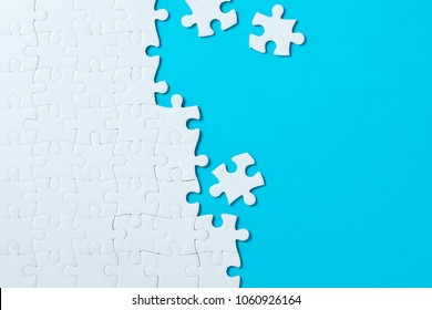 Unfinished white jigsaw puzzle pieces on blue background