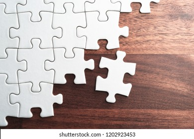 Unfinished white jigsaw puzzle pieces on wood table.