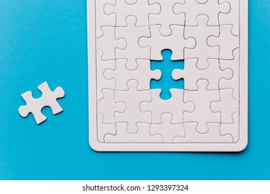 Unfinished white jigsaw puzzle pieces. One missing jigsaw piece on blue background