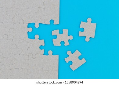 Unfinished white jigsaw puzzle pieces on blue background.