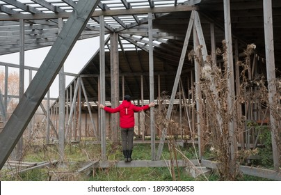 Unfinished wooden building. Woman standing on a bar in the unfinished wooden construction.