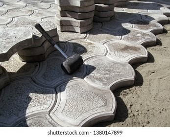 Unfinished work on laying paving slabs 'Bikini'. A mallet leans on a pile of tiles and an uneven edge of paving slabs laid on a dry cement-sand mix, background with copy space