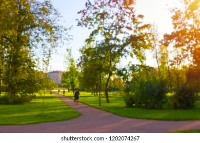 Unfocused blurred bright autumn photo in the park. Modern urban contrast defocused photo. Old street in autumn mood. Golden hour