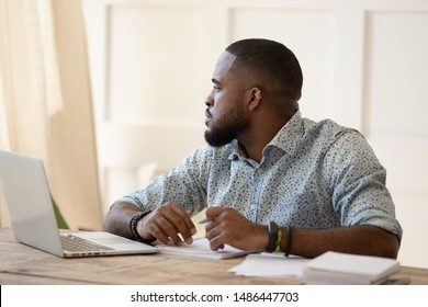 Unfocused bored tired black young man feeling bored during remote work or online courses study, having lack of motivation or energy. Overworked black guy feeling lazy, having monotonous job.