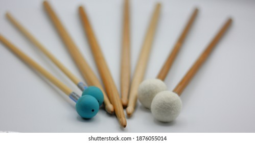 Unfocused percussion mallets set on a white background.
