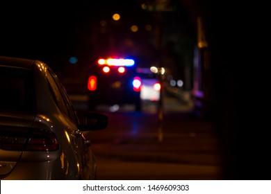 Unfocused police vehicle on urban street in dark