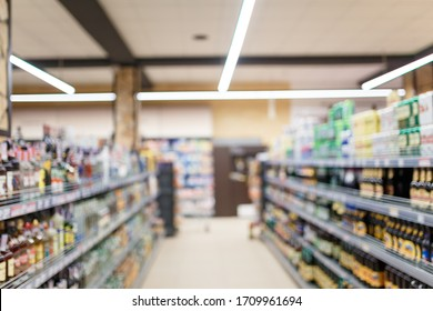 Unfocused shot of supermarket interior. Blurry hypermarket, mall or shopping center background. Rows and shelves of grocery department with alcohol drinks.