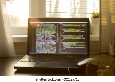 Unfocused web development code in sunset rays. Web developer workspace in the light of sunset rays. Blurry  abstract information technology background.