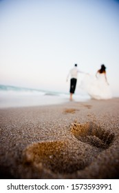 Unfocused wedding couple in the background walking along the beach and leaving their footprints.