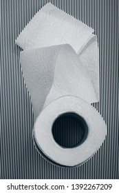 unfolded roll of toilet paper on a striped background.