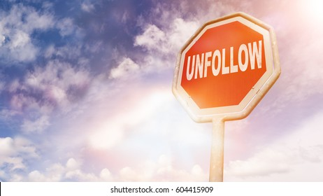 Unfollow, text on red traffic stop sign in front of cloudy blue sky with lens flares