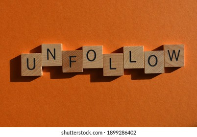 Unfollow, word in wooden alphabet letters isolated on orange background with room for text
