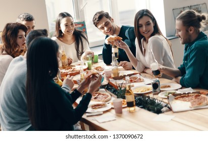 Unforgettable party. Group of young people in casual wear eating pizza and smiling while having a dinner party indoors