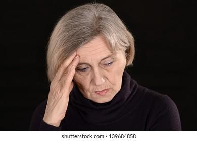 unfortunate senior woman thinking on a black background