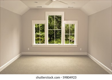 unfurnished attic bedroom with view windows