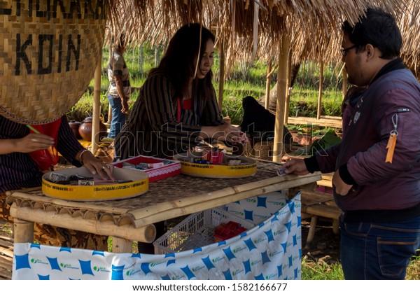 Ungaran, Central Java, Indonesia - December 8, 2019: Tourists exchange money for coins at Sawahan Market, Kalongan, Ungaran.