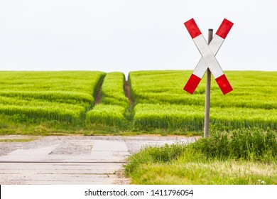 Unguarded railroad crossing with saltire sign at lonely rural way, no train passing, green agricultural field in spring (copy space)/Railway Crossing at Countryside