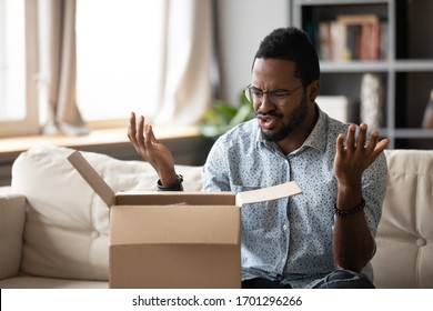 Unhappy African American man client disappointed with product quality shopping online, mad biracial male open cardboard package frustrated with wrong Internet order, bad delivery service concept