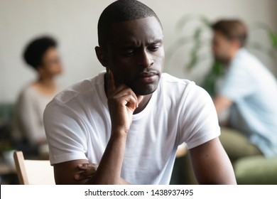 Unhappy african American millennial guy sit alone in coffeeshop thinking lack friends, upset sad biracial male outcast or loner feel offended hurt pondering having communication problem