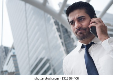 unhappy asian business man talking smart phone; portrait of unhappy sad failed serious Asian, Indian businessman talking via smart phone; negotiation, business deal, transaction, communication concept