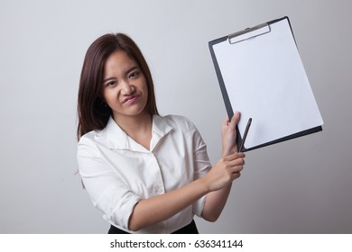 Unhappy Asian business woman point to clipboard with pen on white background