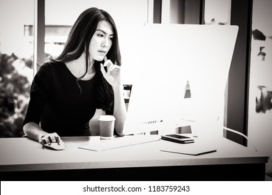 Unhappy  asian business woman working in modern office. Serious  asian girl using computer in workplace. Beautiful businesswoman, coffee, seriously
