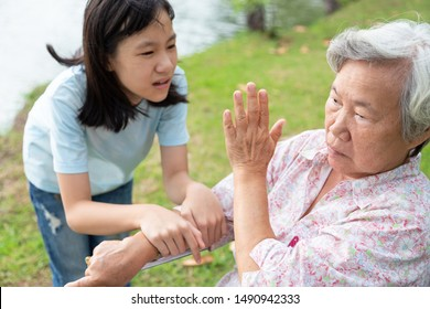 Unhappy asian child girl comfort upset offended senior grandmother,female teenager is stressed to trying to reconcile or compromise,elderly people looking away avoiding talking with granddaughter