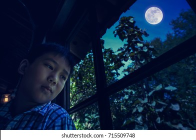 Unhappy asian child sitting near window and looking aside while feeling sad. Handsome boy feel lonely, kid emotion. Nighttime with full moon on sky. Dark tone.