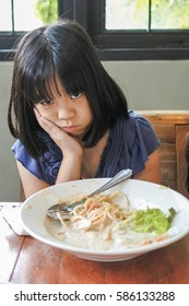 Unhappy Asian girl kid getting bored of food with appetite loss, no hungry habit, eating disorder