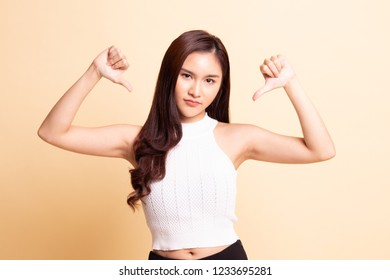Unhappy Asian girl show thumbs down with both hands   on beige background