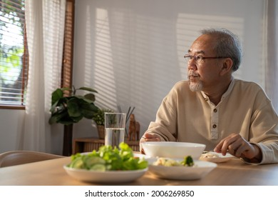 Unhappy Asian Senior older man sit alone, eat foods on table in house. Depressed mature attractive elderly retired grandfather stay at home with painful face feeling upset, lonely and miss his family.
