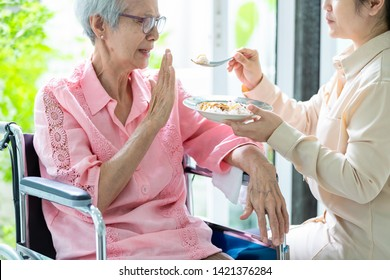 "Unhappy asian senior woman rejecting,gesture hand ""NO"" elderly patient bored with food or boredom,old people getting sick and tired of food in wheelchair at home,loss of appetite,anorexia concept"
