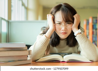 Unhappy Asian woman boring to read a lot of books at unversity library. Student studying hard exam in a library.