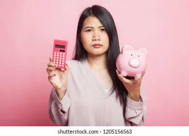 Unhappy Asian woman with calculator and piggy bank on pink background