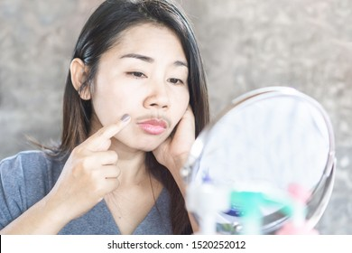 unhappy Asian woman having problem with mustache growing on face