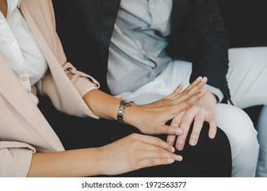 Unhappy asian young employee woman defending at hand of colleagues, man or boss touching her knee feeling disgusted and uncomfortable. Sexual harassment inappropriate at office, workplace concept.
