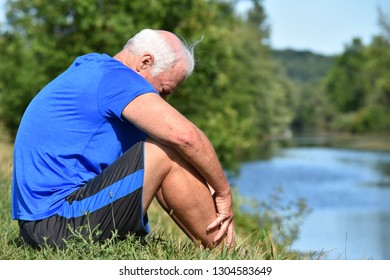 Unhappy Athletic Grandfather Sitting By River