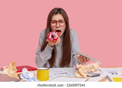 Unhappy attractive young woman cries as has problems at work, eats tasty sweet donut, carries modern touchpad, develops business strategy, studies graphs, drinks tea, models over pink studio wall