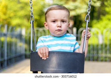 Unhappy baby boy looking at camera on the swing in the park