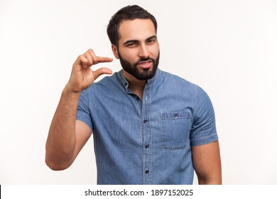 Unhappy bearded man looking disappointed and showing a little bit gesture, small amount or low scale sign, few centimeters. Indoor studio shot isolated on white background