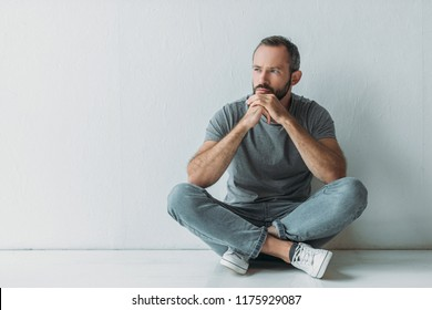 unhappy bearded man sitting in floor and looking away