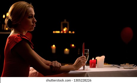 Unhappy beautiful lady sitting alone in restaurant, boyfriend late for dinner