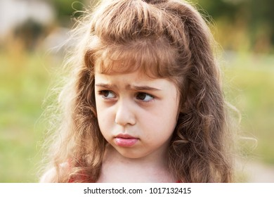 Unhappy beautiful little Girl is crying outdoors