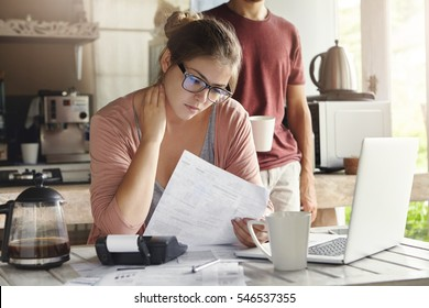 Unhappy beautiful woman wearing spectacles having concentrated look reading notification form bank on debt, sitting at kitchen table in front of open laptop, her husband drinking coffee on background