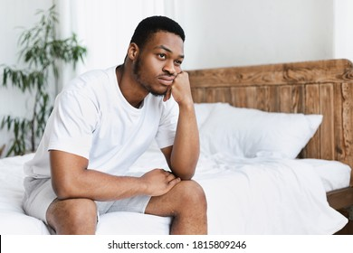 Unhappy Black Guy Sitting On Bed In Bedroom At Home. Depressed African American Man Thinking Of Life Problems. Stress, Apathy And Male Depression Concept. Free Space For Text