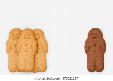 Unhappy black  and white gingerbread men being isolated from a group on an isolated white background representing racial segregation and discord.