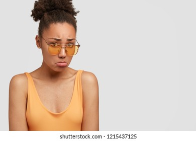 Unhappy black woman sulks from sadness, purses lower lip, has displeased facial expression, recieves bad news, isolated over white background with copy space for your advertisement or promotion