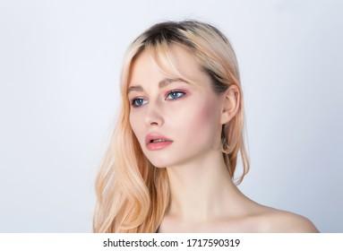Unglückliches blondes Mädchen mit übergewachsenen dunklen Haarwurzeln.