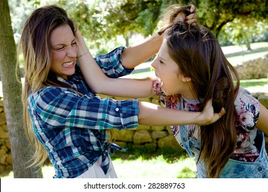 Unhappy blonde girls fighting angry pulling long hair